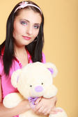 Childish young  infantile girl in pink hugging teddy bear toy — Stock Photo