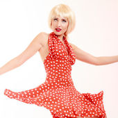 Beautiful pinup girl in blond wig and retro red dress dancing — Stock Photo