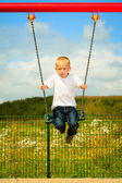 Little blonde boy having fun on a swing outdoor — Stock Photo
