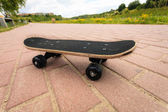 Lone skateboard deck outdoor on paving stone — Stock Photo