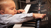 Boy  playing on digital keyboard piano synthesizer — Stock Photo