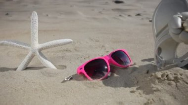 Colorful sunglasses, flip flops and starfish seastar on the sandy beach — Stock Video