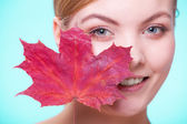 Portrait of young woman with red maple leaf. — Stock Photo