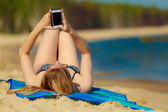Summer vacation Girl with phone tanning on beach — Stock Photo