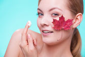 Face of young woman with red maple leaf. — Stock Photo