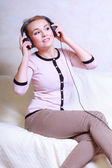 Modern woman with headphones listening to music — Stockfoto