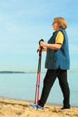 Active woman senior nordic walking on a beach — Stock Photo