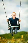 Little blonde  child having fun on a swing outdoor — Stock Photo
