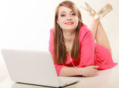 Girl with headphones and laptop listening to music — Stockfoto