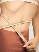 Weight loss, measuring tape on woman waistline — Photo