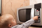 Boy  playing with timer of microwave oven — Stock fotografie