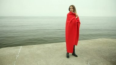 Sad pensive woman in red blanket standing on the sea shore — Stock Video