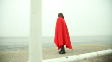 Sad pensive woman in red blanket looking at the sea or ocean — Stock Video