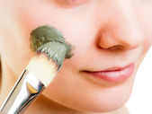 Woman applying clay mud mask on face. — Stockfoto