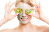 Woman in clay mask with kiwi on face — Stock Photo