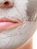 Woman applying clay mask on face. — Stock Photo