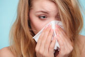 Sick girl sneezing in tissue. — Foto de Stock