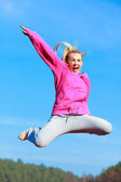 Cheerful woman in tracksuit jumping showing outdoor — Φωτογραφία Αρχείου