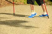 Active senior legs in sneakers nordic walking in a park. — Stock Photo