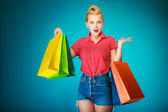 Pinup girl with shopping bags buying clothes — Stock Photo