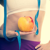 Fit girl with measure tape, fruit apple. — Stock Photo