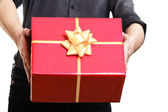Man giving red gift box with golden ribbon — Stock Photo