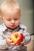 Little boy eating apple fruit at home — Stock Photo