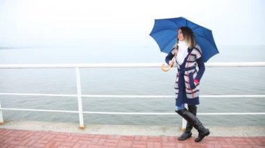 Young woman with blue umbrella relaxing on the pier in rainy day — Vídeo Stock