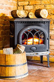 Fireplace with fire flame and firewood in barrel interior. — Stock fotografie