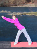 Woman in tracksuit doing exercise on pier outdoor — Stock Photo