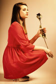 Fashion woman teen girl in red gown with dry rose. — Stock Photo