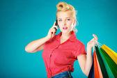 Fille de pin-up avec des sacs appelant sur le téléphone — Photo