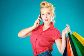 Pinup girl with shopping bags calling on phone — 图库照片