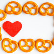 Frame of pretzels and red heart white background — Stock Photo #50271749