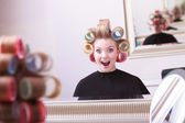 Cheerful happy blond girl hair curlers rollers hairdresser beauty salon — ストック写真