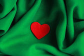 Red wooden decorative heart on green folds background. — Stock Photo