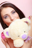 Childish young woman infantile girl in pink kissing teddy bear toy — Stock Photo