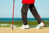 Nordic walking. Female legs hiking on the beach. — Stock Photo