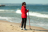 Nordic walking. Woman hiking on the beach. — Stock Photo