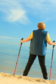 Woman senior nordic walking on a beach — Stock Photo