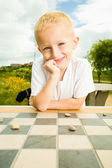 Child playing draughts or checkers — Stock Photo