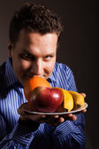 Diet nutrition. Happy young man smelling fruits. — Foto de Stock