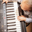 Child playing on digital keyboard piano — Stock Photo