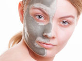 Woman applying clay mask on her face — Stock Photo