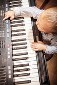 Child playing on digital keyboard piano — Stock Photo