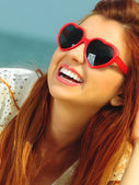 Redhaired girl in sunglasses on beach — Stock Photo