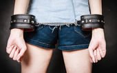Leather handcuffs on hands prisoner girl — Stock Photo