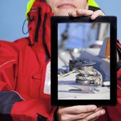 Sailor showing yacht on tablet — Stock Photo