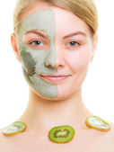 Woman in clay mask on face and kiwi — Stock Photo