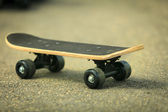 Lone skateboard deck on asphalt — Stock Photo